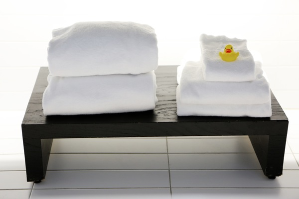 stacked towels and a rubber ducky on a bathroom stand