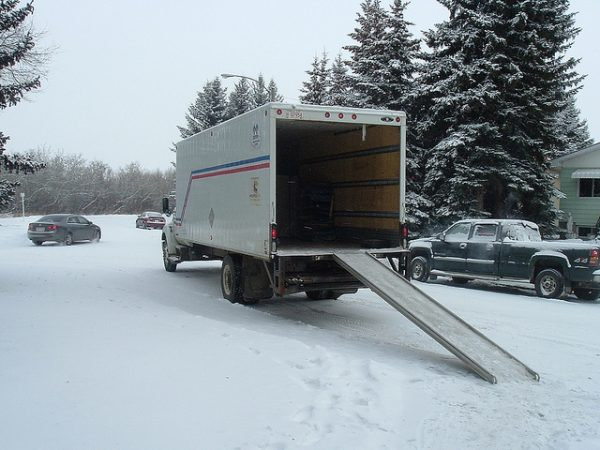 moving truck with a ramp extended onto the snow