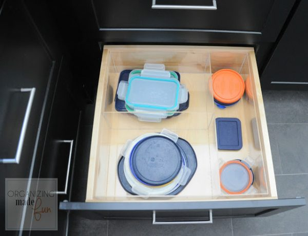 organize tupperware lids in a kitchen drawer with acrylic organizers