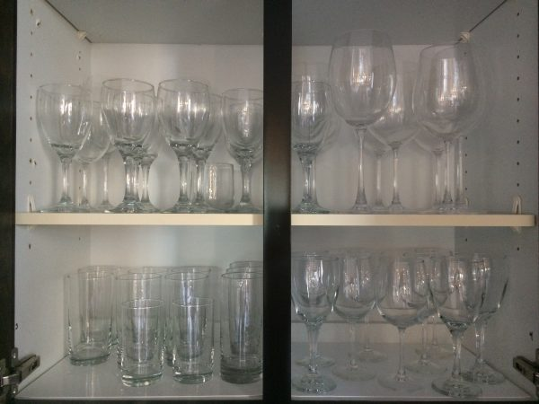 glasses standing up on shelves in kitchen cabinets