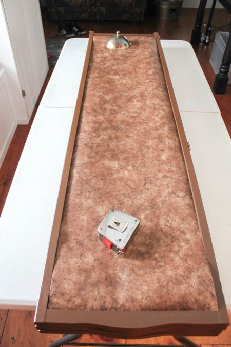 room divider panel with mottled brown wallpaper and a tape measure on top