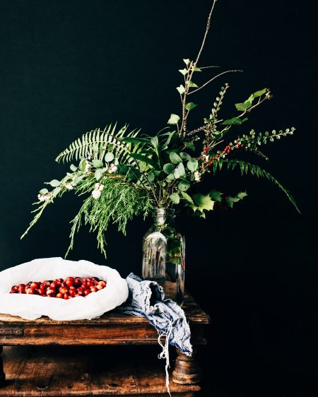 hygge plants, including a fern and red berries
