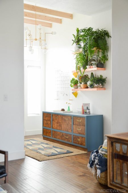 entryway makeover consisting of copper floating shelves, potted plants, and a console with drawers
