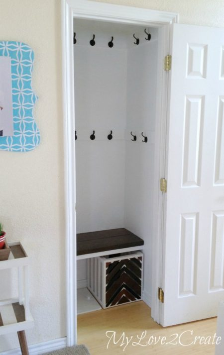 hall closet makeover with wall hooks, a bench, and a storage crate
