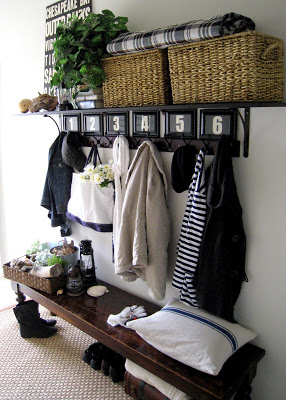 entryway bench with numbered coat hooks, a shelf, and baskets for storage
