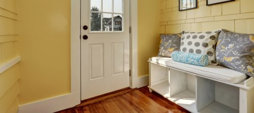 entryway storage hacks, ideas, and solutions: white storage bench with cubbies, wheels, a cushion, and pillows