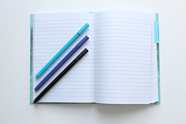 light blue, royal blue, and black pens atop an open light blue notebook