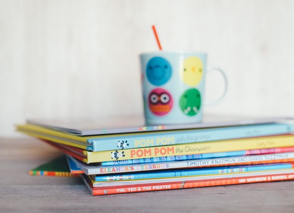 kids mug atop a stack of children's books