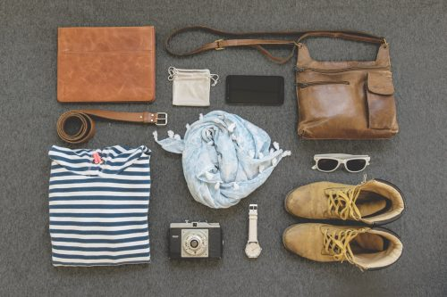 clothes, boots, cell phone, belt, sunglasses, camera, watch, bag, binder, and pouch organized neatly
