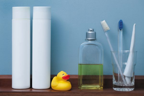 2 white bottles and a rubber ducky, cologne bottle, and glass toothpaste and toothbrush holder on a wooden bathroom shelf