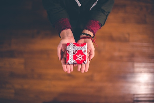 hands giving a holiday gift to someone