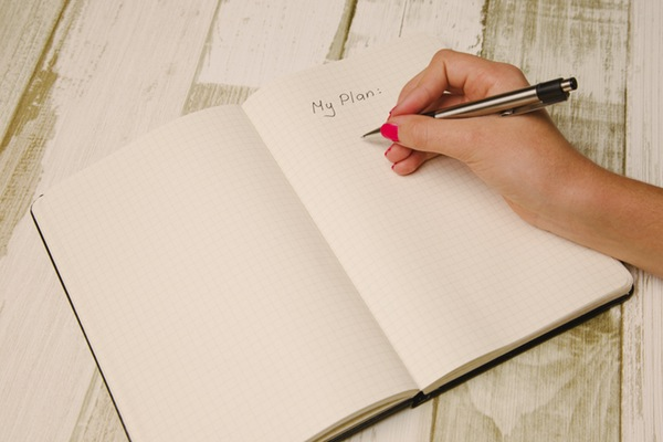 "a woman's hand writing ""my plan"" in a notebook"