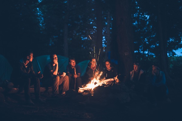 people sitting in front of a bonfire