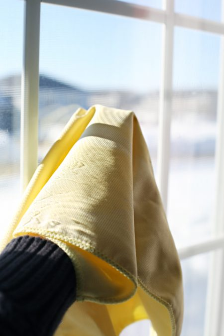 cleaning a window with a yellow glass polishing rag