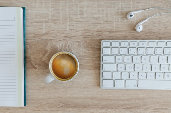 overhead view of a clean wooden workspace with a notebook, coffee mug, magic keyboard, and earpods