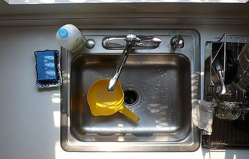 a yellow strainer in a clean kitchen sink