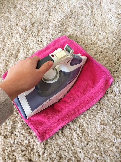 paige smith removing carpet stains with an iron and a wet pink rag