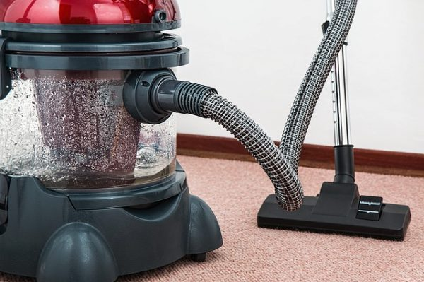 red and black hoover vacuum cleaner on a carpet