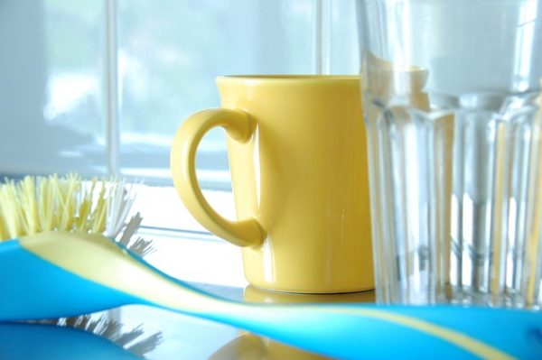clean yellow coffee mug, drinking glass, and dish brush in a kitchen