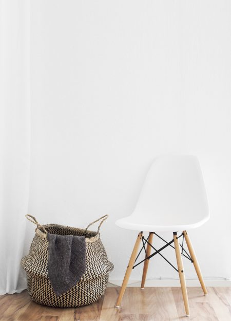 laundry basket next to a white eames style vortex chair on a wooden floor in a clean home