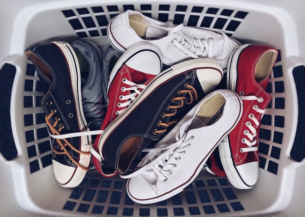 multiple pairs of white, red, and black converse chuck taylors in a laundry basket