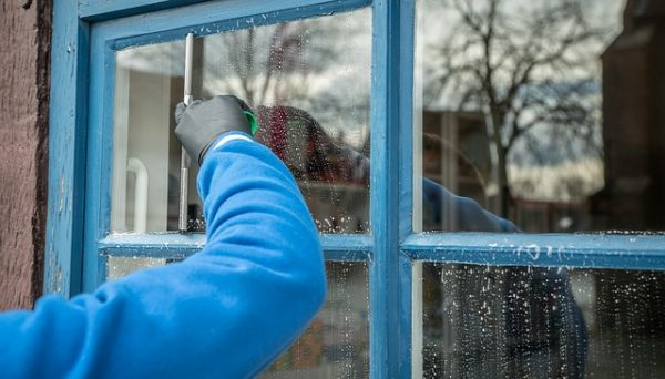 cleaning the outside-facing part of a window with a squeegee