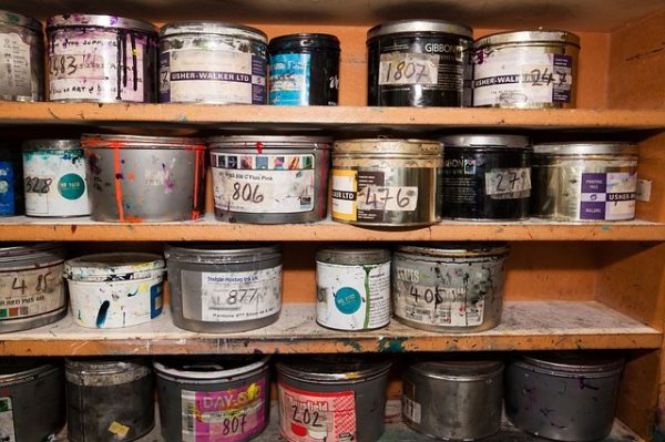 paint cans on four workshop shelves