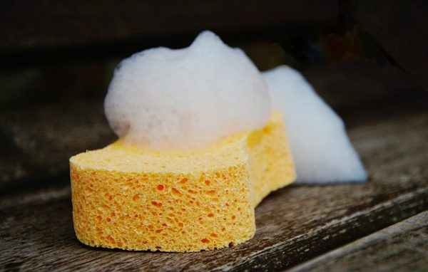 soapy yellow sponge on a wood floor