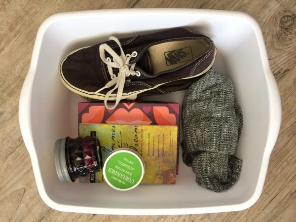 white reuse bin by paige smith storing socks, roiander body butter, a candle, books, and a pair of vans shoes