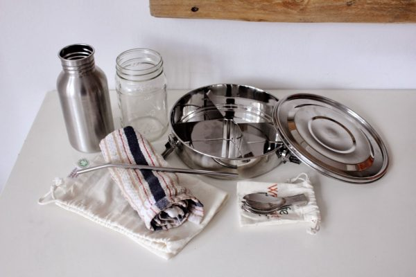 zero waste lunch kit by trash is for tossers includes: a stainless steel lunch container, a reusable fork and napkin, organic cotton bags, a mason jar, and a stainless steel canteen