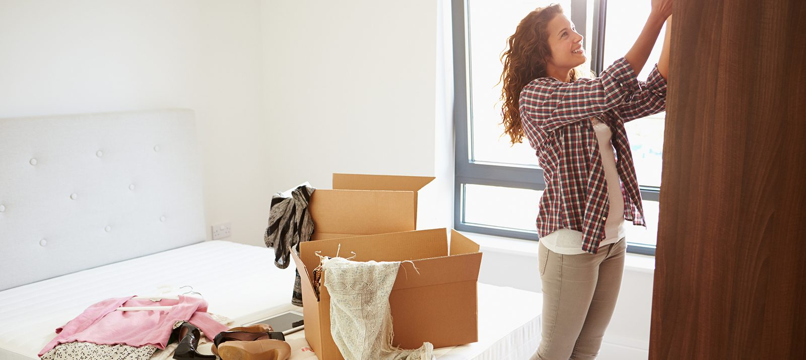 what to store and toss before moving into a new house: a woman packing clothes into boxes in a bedroom