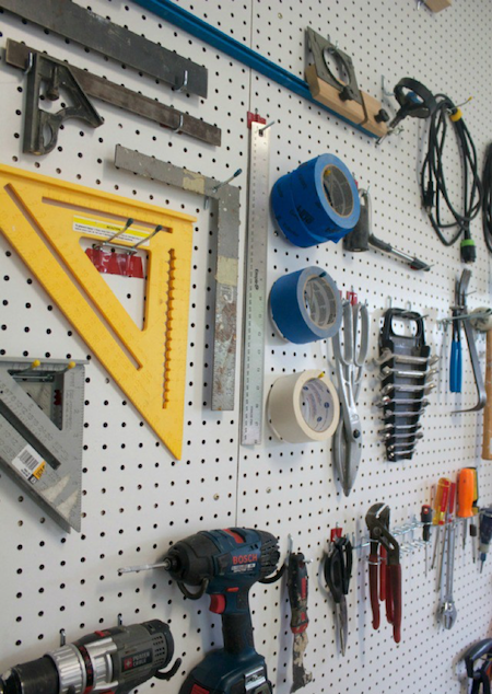 white diy pegboard with hooks storing tools in a garage