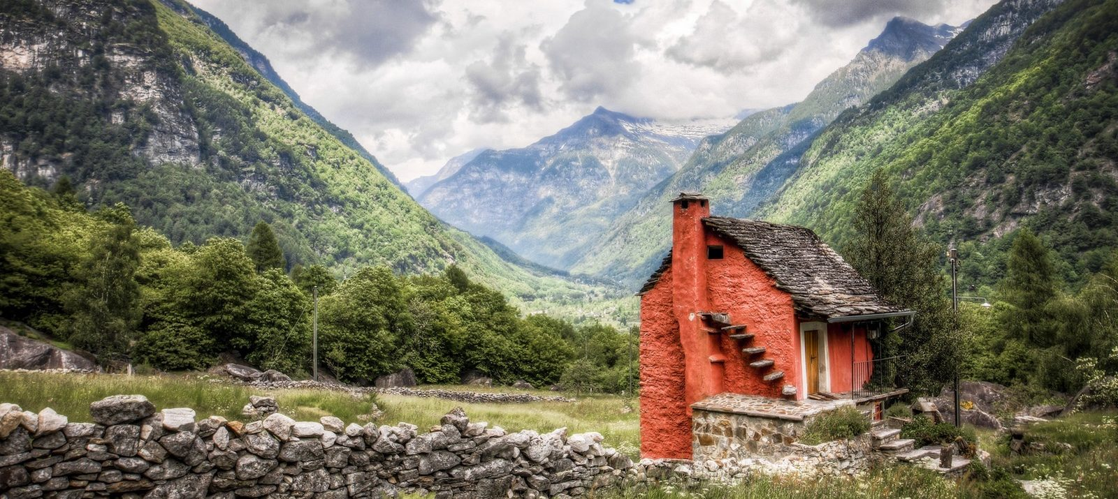 tiny red house on a sunny day with mountains in the background