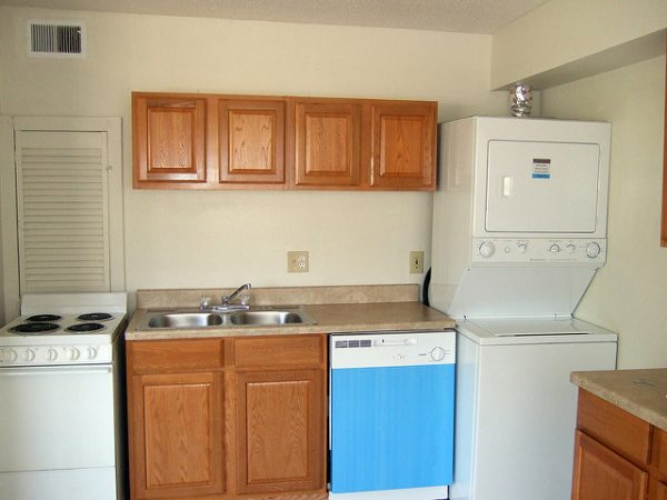 stove, sink, dish washer, and an all-ine-one washer dryer crammed next to each other in a small kitchen