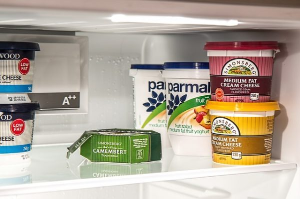 cheese, cream cheese, and yogurt containers on a fridge shelf