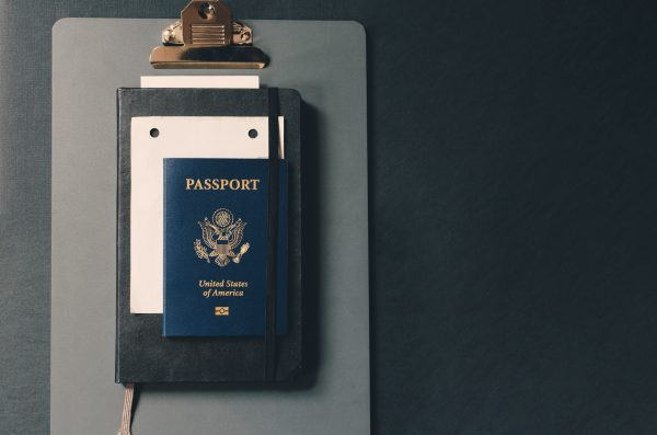 us passport atop a small sheet of paper, a small notebook, and a clipboard