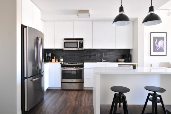 modern apartment kitchen with a fridge, freezer, stove, oven, microwave, 2 coffee makers, a kitchen island, and 2 stools