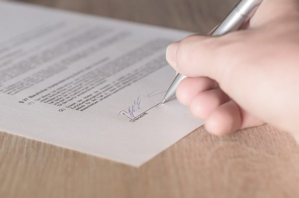 hand signing apartment lease with a pen