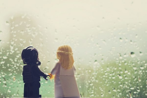 lego star wars characters holding hands and looking through a window on a rainy day