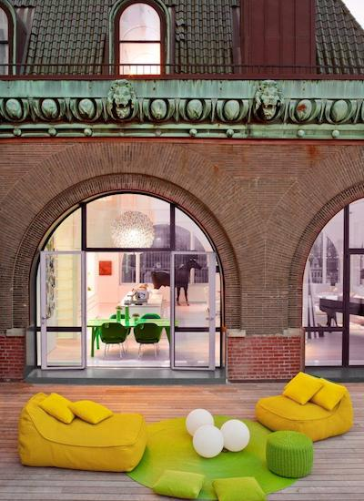 ghislaine vinas' fun outdoor decor: 2 mustard outdoor seats, a green circle rug with 3 giant ping pong balls on top, and a green ottoman