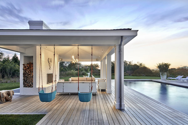 ghislaine vinas' poolside patio with a fireplace, 3 sofas, and 2 outdoor hanging chairs