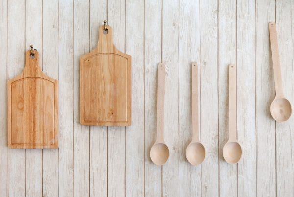 2 wooden cutting boards and 4 cooking spoons hanging on wall-mounted hooks