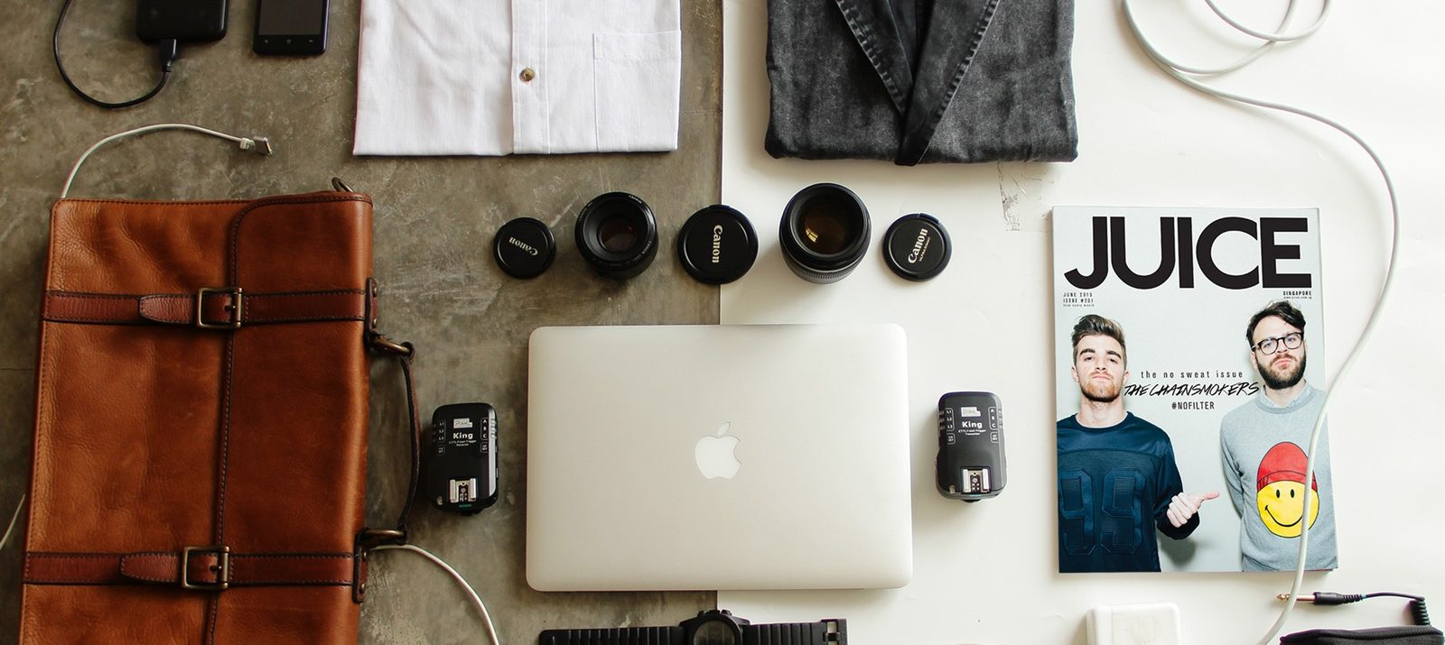 organizing your stuff: leather bag, macbook, watch, shirts, shoes, a magazine, photography accessories, cords, pencils, and a pen