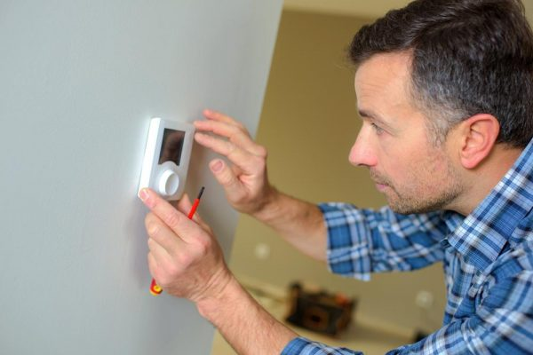 man changing thermostat
