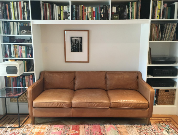 brown leather sofa surrounded on all sides by a bookcase