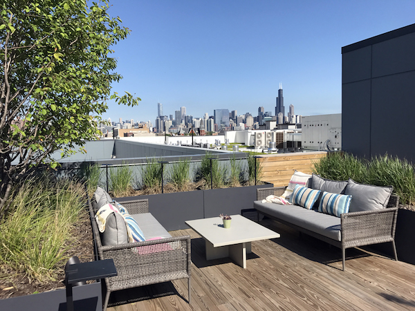 brianne bishop's luxe on chicago rooftop project scene 2: a coffee table in the middle of two outdoor benches facing eachother