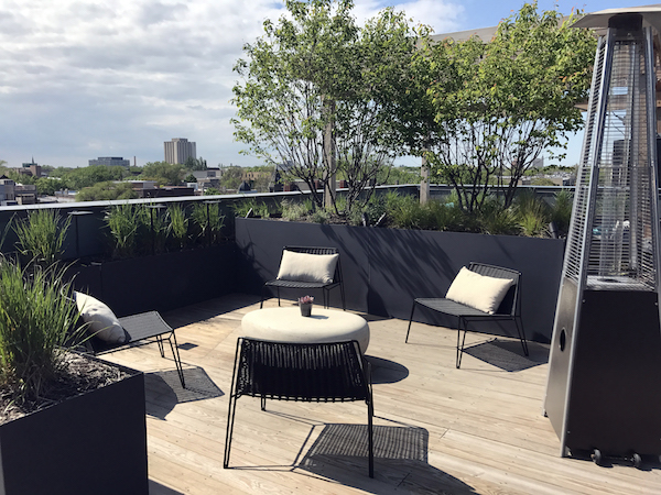 brianne bishop's luxe on chicago rooftop project scene 3: a circular coffee table surrounded by 4 outdoor chairs with pillows