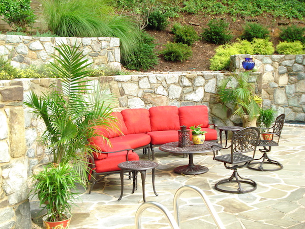june shea backyard seating with red cushions, 2 side tables, a coffee table, and 2 outdoor chairs
