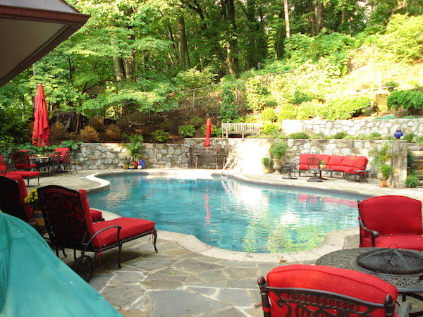 june shea backyard seating with red cushions, outdoor tables and umbrellas, and a pool