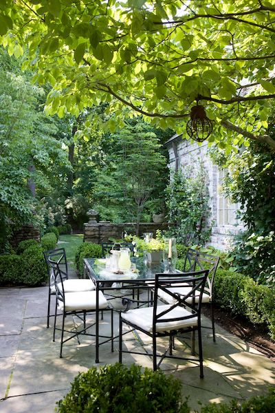 outdoor dining table and chairs with cushions on a backyard patio designed by kelley proxmire